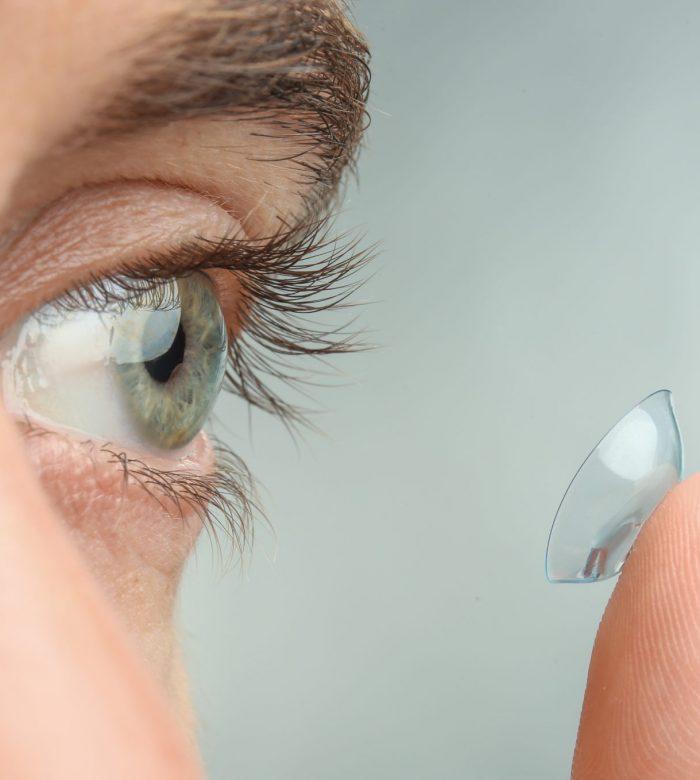 Young man putting contact lens in his eye, closeup